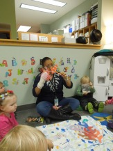 Toddlers learning about symbiotic relationships through the use of puppets and songs about the relationship between anemones and clown fish.