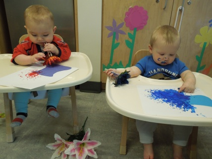 Infants learning about flowers explore painting with silk flowers. The sensation of touching and tasting is just as exciting as the experience of squishing the painted flowers onto the paper.