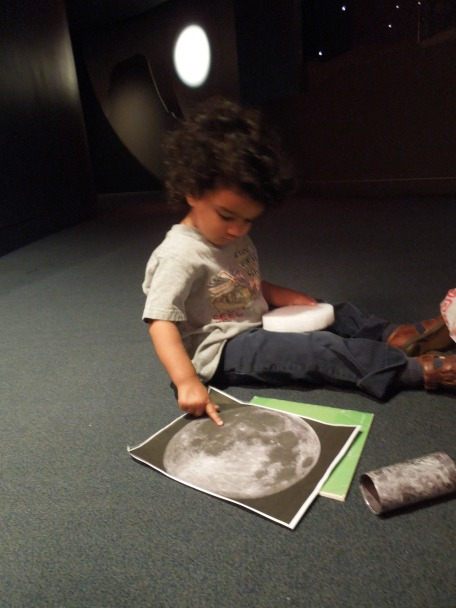 Toddlers closely examining the moon at the National Museum of the American Indian.