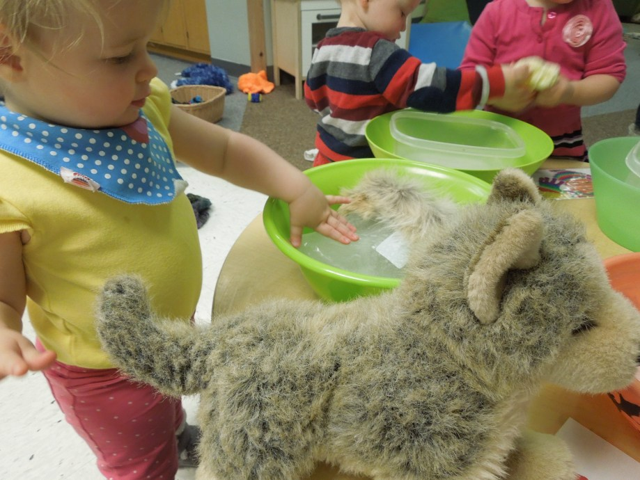 Toddler touching ice with stuffed animal.