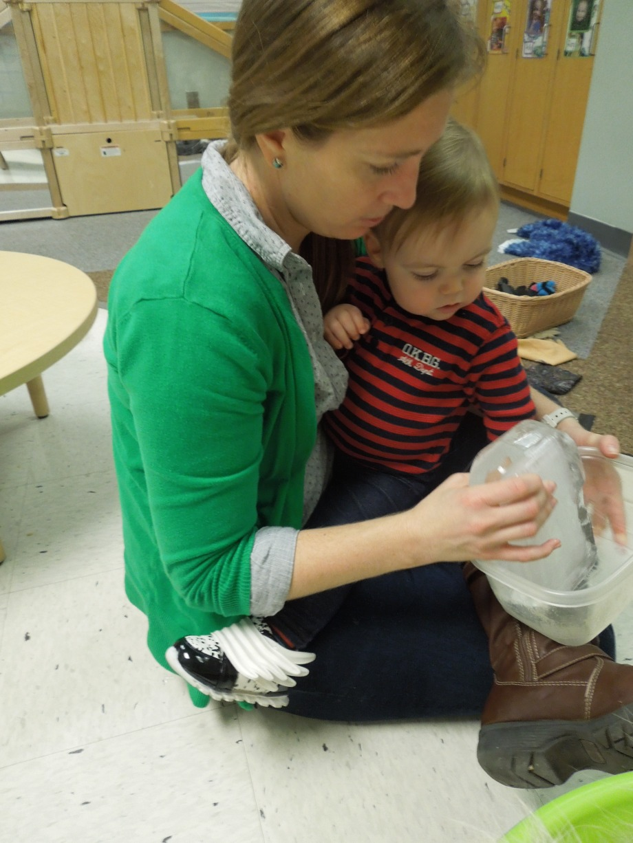 Toddler and teacher holding block of ice together.