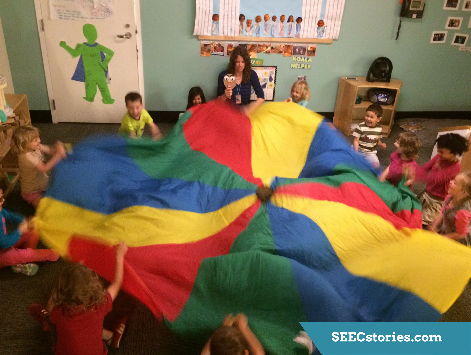 Children sitting in a circle throwing up a parachute