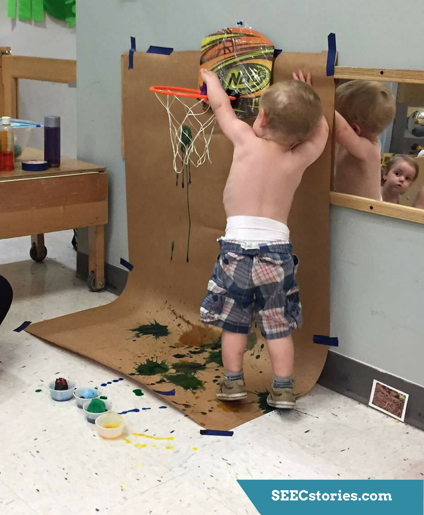 A toddler dunks a pom pom with paint on it into a little basketball hoop with butcher paper behind it. The butcher paper has paint on it.