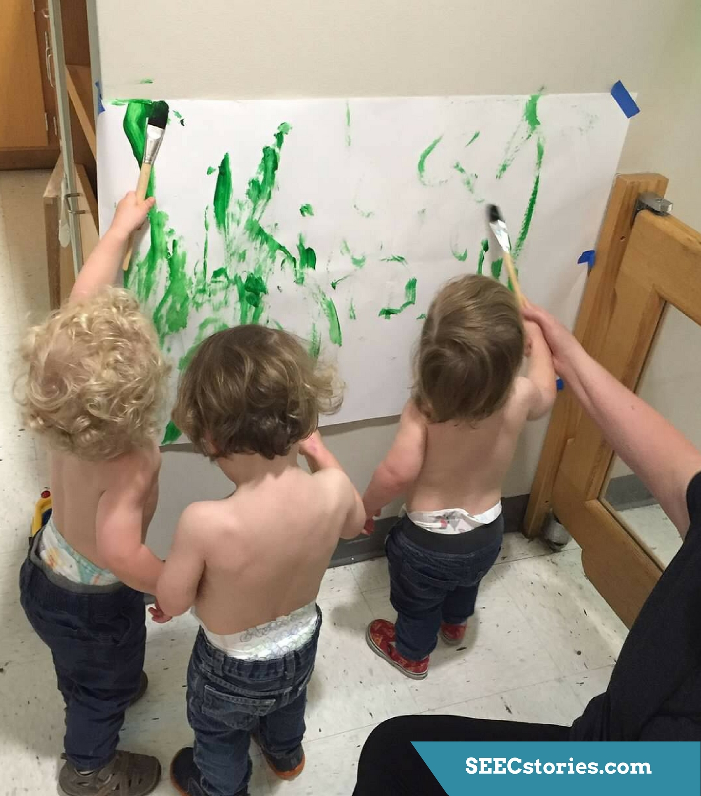 Three toddlers use paintbrushes to put green paint on a piece of large paper that is taped to the wall.