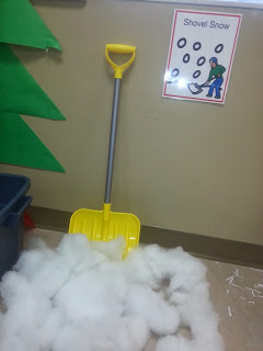 A pile of cotton stuffing on the ground with a shovel propped up next to it.