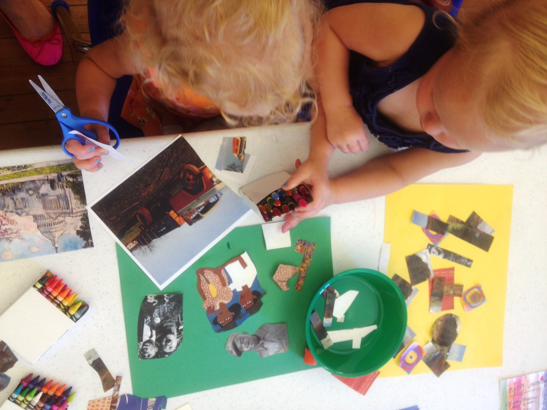 Two children cutting out images and placing on construction paper