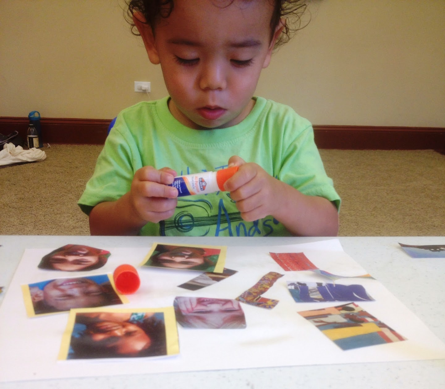 Child holding a glue stick, pasting images to a piece of paper
