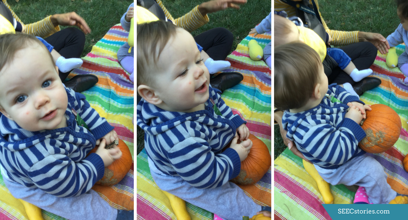 A child sitting on a picnic blanket holding a pumpkin