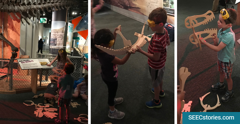 Children looking at and holding pretend dinosaur bones