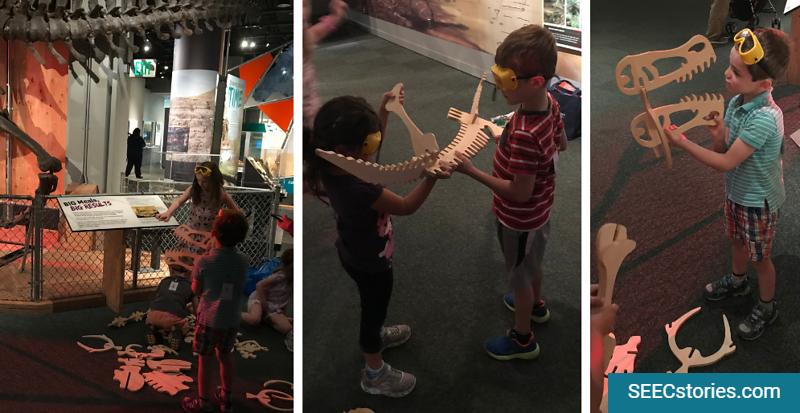Children looking at and holding pretend dinosaur bones