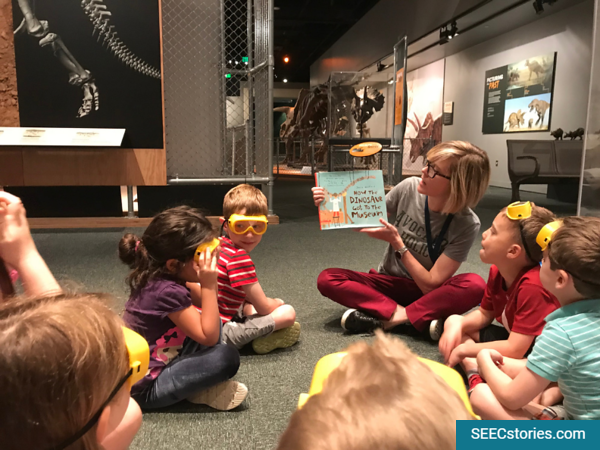 Children sitting in a circle listening to a book about dinosaurs