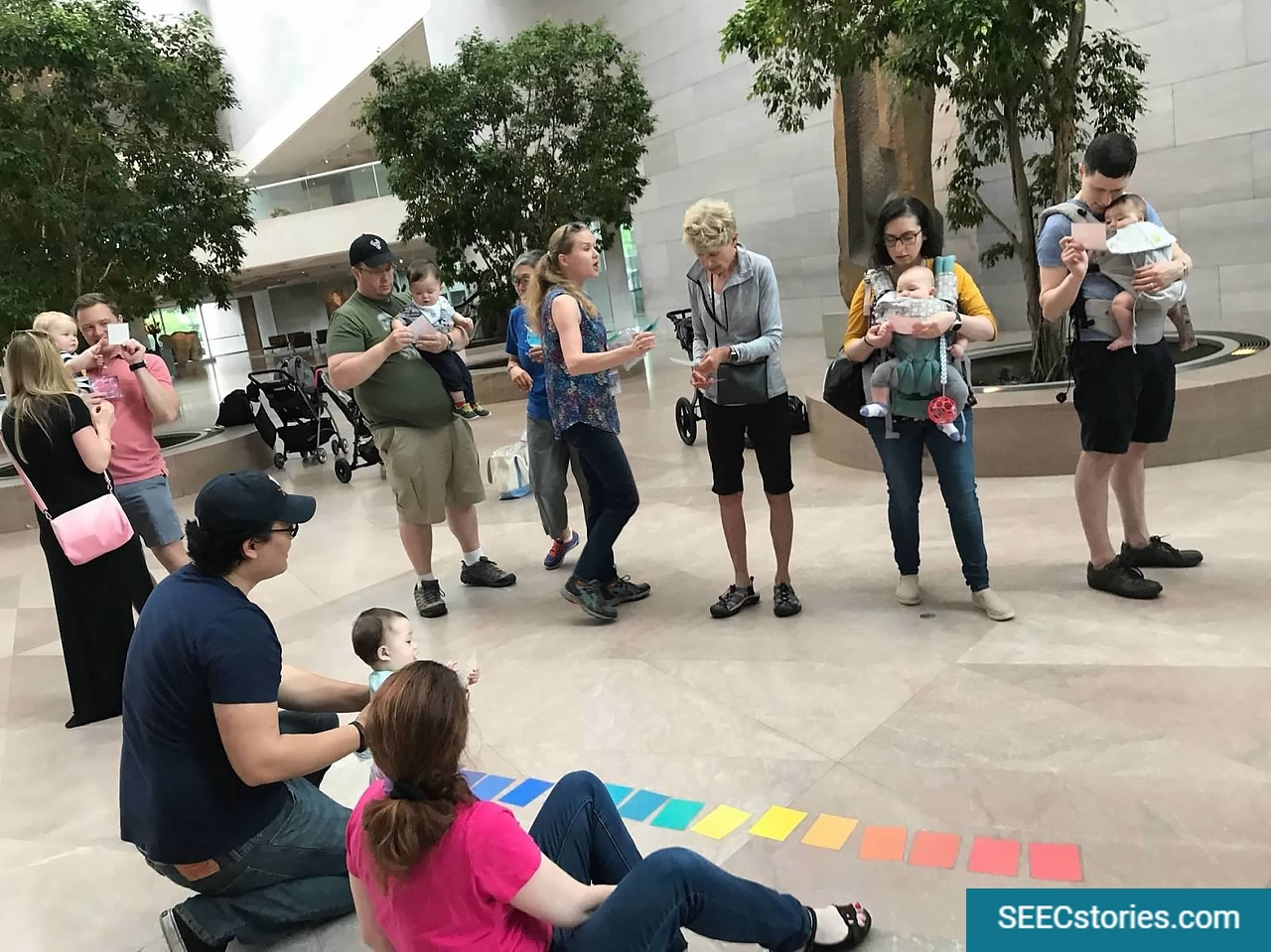 Parents standing in a circle looking down at a series of colored squares aligned on the floor