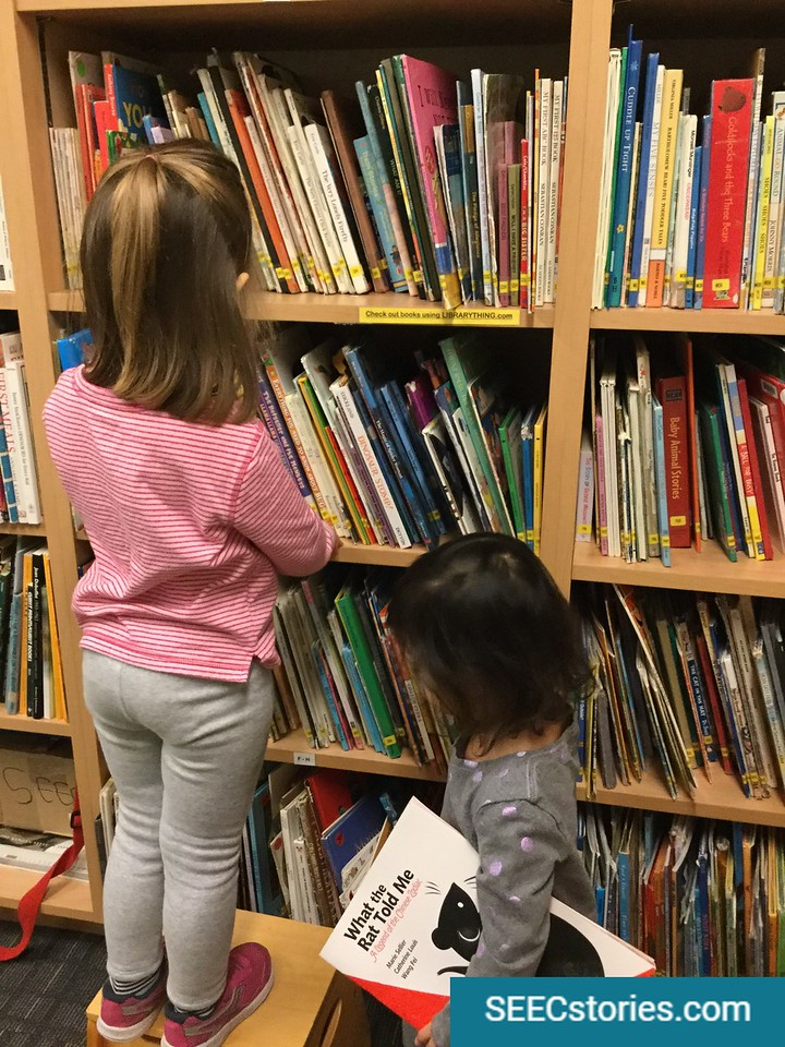 Two children putting books back on a shelf in the library