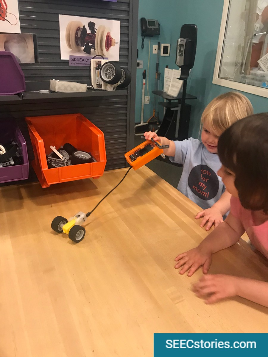 Two children playing with a set of wheels attached to a battery