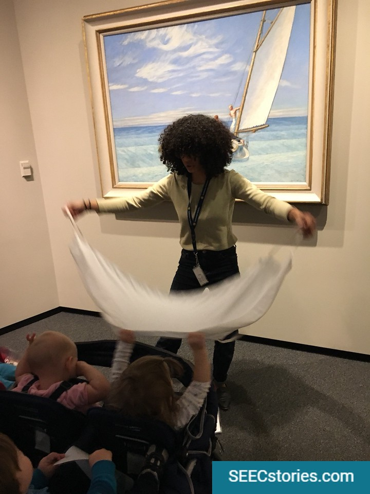 Teacher holding a sail, holding it up for children in stroller to see