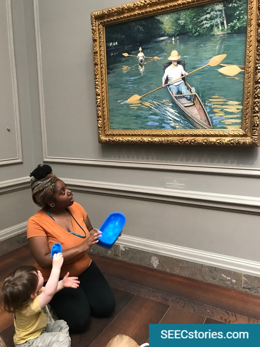 Teacher and child holding boats looking at a painting of a boat