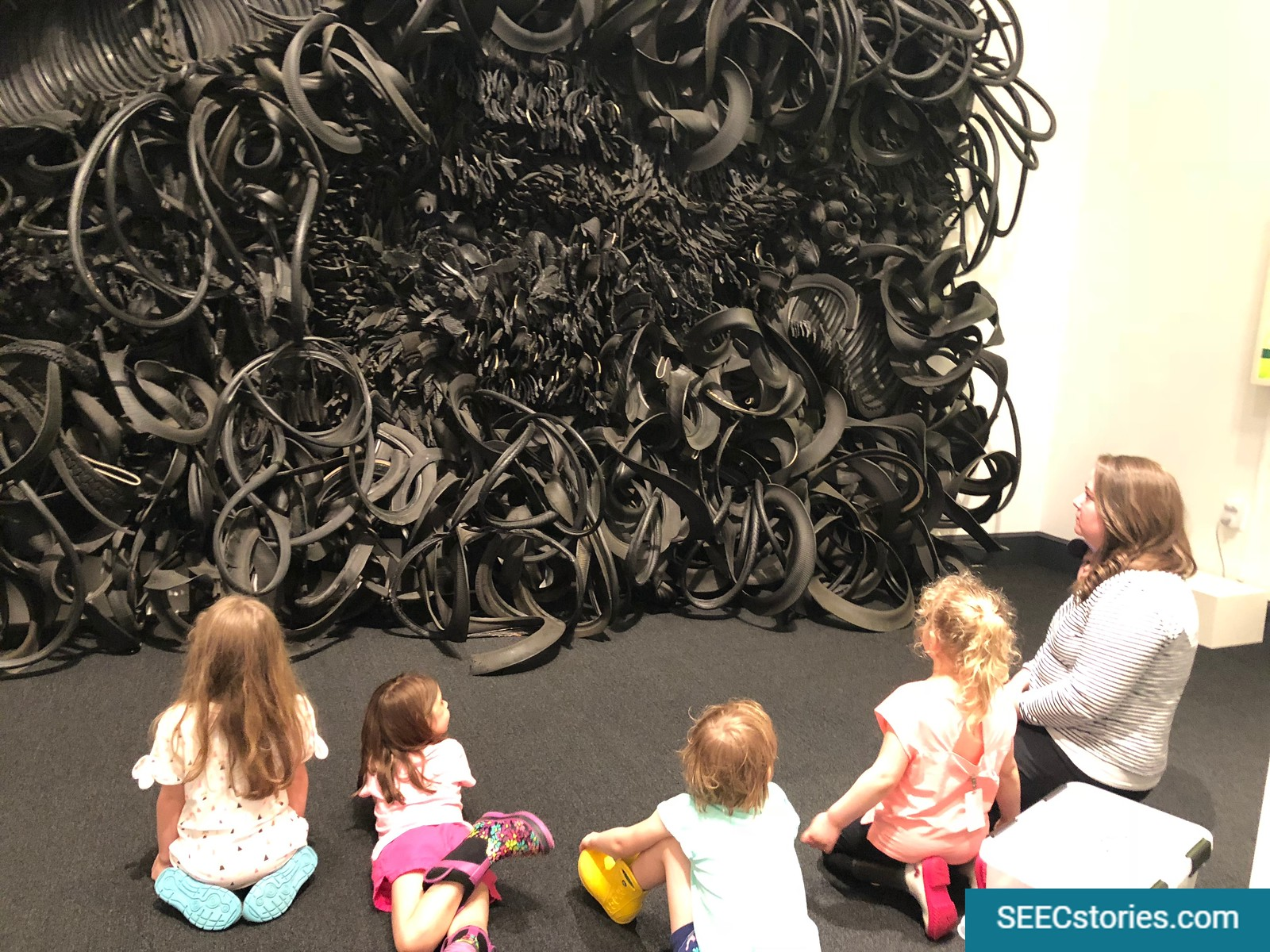 A group of four children look at an artwork with a museum educator at the National Museum for Women in the Arts.