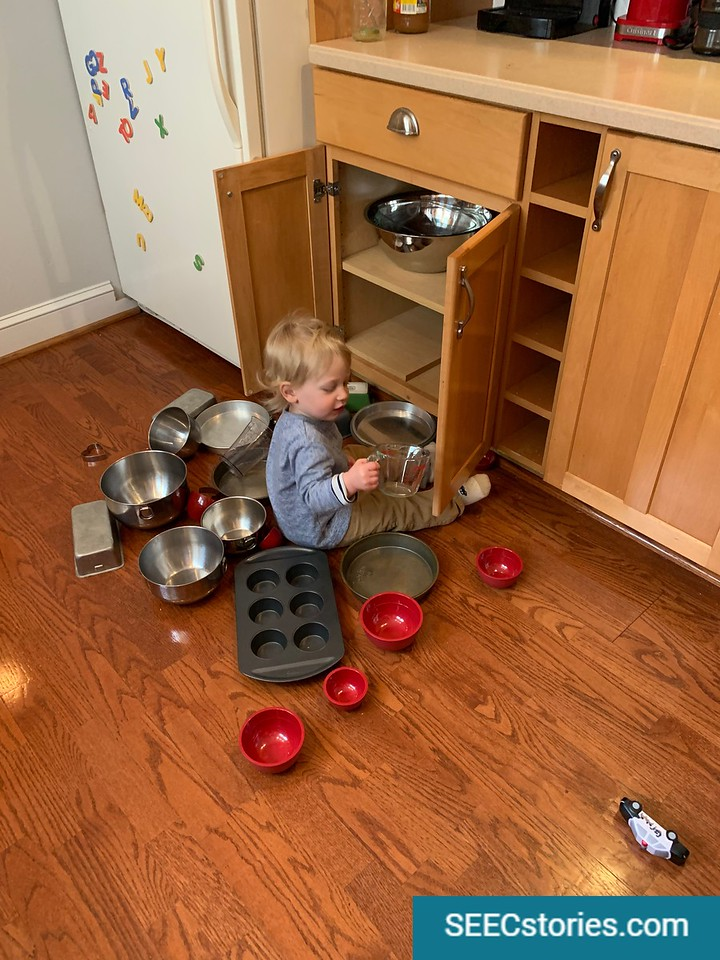 A young child sits in front of an open cabinet, pulling out bowls, measuring cup, and pans.