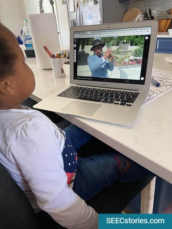 A young child sits on a chair looking at a computer in which a photo is displayed of a man playing a trumpet.
