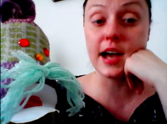 An educator holding up and interacting with a sock puppet.