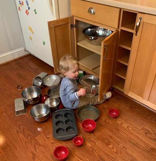 a child sitting in front of an open kitchen cabinet, pulling out kitchen tools such as bowls, measuring cup, and cupcake pan.