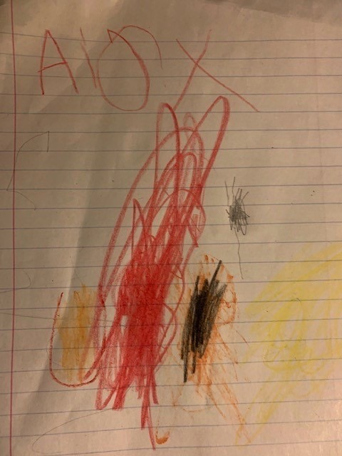 A drawing with red, orange, yellow and black crayon.
