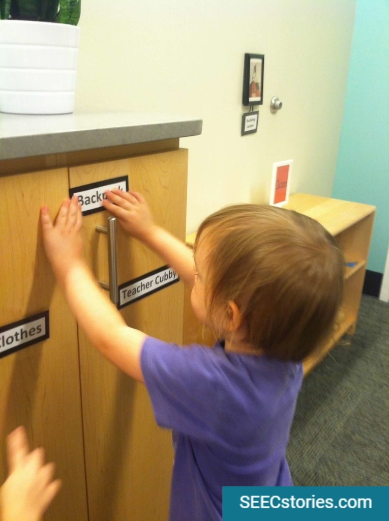 "A child puts up the label ""backpack"" on a cubby in a classroom. Two labels are seen below: ""clothes"" and ""Teacher Cubby""."
