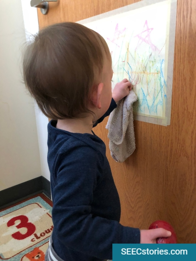 A child uses a small towel to wipe a door.